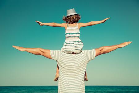 Vader en kind met plezier op het strand. Zomer vakantie en reizen concept