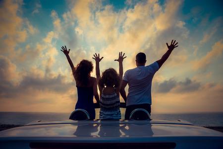 Silhouette der Familie am Strand entspannen. Leute, die Spaß im Cabriolet gegen den blauen Himmel im Hintergrund. Sommer-Urlaub und Reise-Konzept