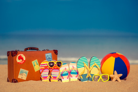 sun beach: Vintage suitcase and flip-flops on sandy beach against blue sea and sky background. Summer vacation concept