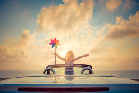 Silhouette of child relaxing on the beach. Person having fun in cabriolet against blue sky background. Summer vacation and travel concept Foto de archivo