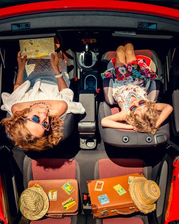 viaje familia: recorrido de la familia feliz en coche. Mujer y niño que se divierte en descapotable rojo. vacaciones de verano y el concepto de viaje. Vista superior Foto de archivo