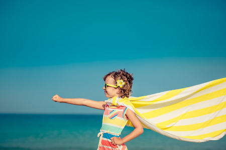 Child having fun on the beach against sea and sky background. Summer vacation and travel concept