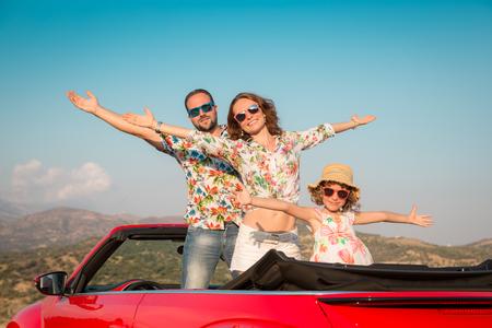 recorrido de la familia feliz en coche en las montañas. Las personas que se divierten en descapotable rojo. concepto de vacaciones de verano