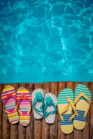 Flip-flops on wood against blue water background. Summer vacation concept Stock Photo