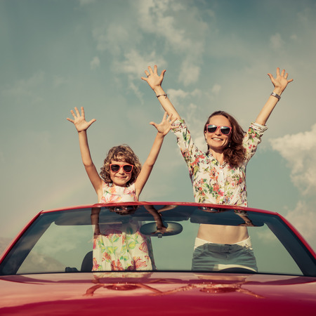family vacation: Happy family travel by car in the mountains. People having fun in red cabriolet. Summer vacation concept Stock Photo