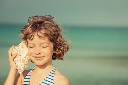 Bambino relax sulla spiaggia contro il mare e il cielo di sfondo. Vacanze estive e concetto di viaggio