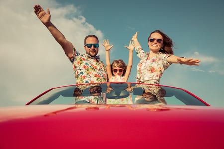 viaje familia: recorrido de la familia feliz en coche en las montañas. Las personas que se divierten en descapotable rojo. concepto de vacaciones de verano
