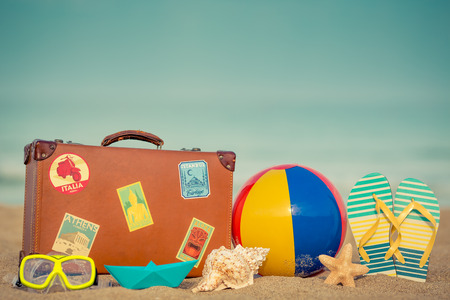 sandy beach: Vintage suitcase and flip-flops on sandy beach against blue sea and sky background. Summer vacation concept
