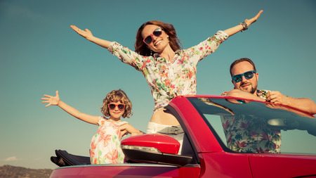 Happy family travel by car in the mountains. People having fun in red cabriolet. Summer vacation concept Reklamní fotografie