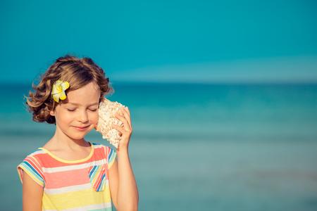 背景に海と空のビーチでリラックスした子。夏休み、旅行のコンセプト 写真素材