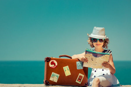 Child with vintage suitcase and city map on summer vacation. Travel and adventure concept Banque d'images