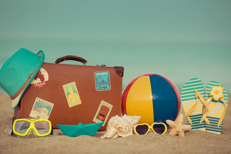 flipflops: Vintage suitcase and flip-flops on sandy beach against blue sea and sky background. Summer vacation concept