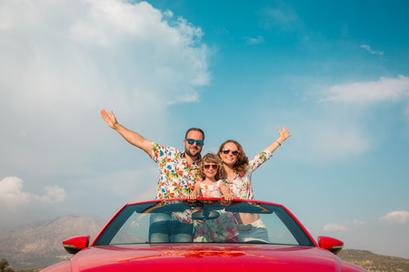 dream car: recorrido de la familia feliz en coche en las montañas. Las personas que se divierten en descapotable rojo. concepto de vacaciones de verano