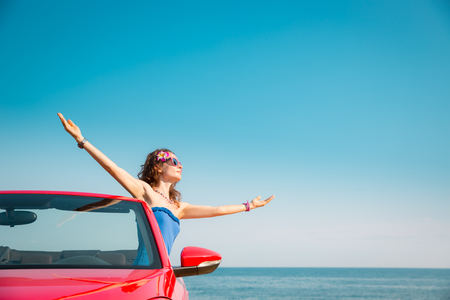 manos levantadas al cielo: Young woman relaxing on the beach. Girl having fun in red cabriolet against blue sky background. Summer vacation and travel concept