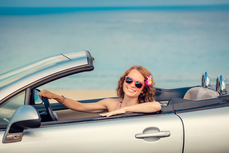 cabriolet: Happy woman travel by car to the sea. Girl having fun in cabriolet. Summer vacation concept