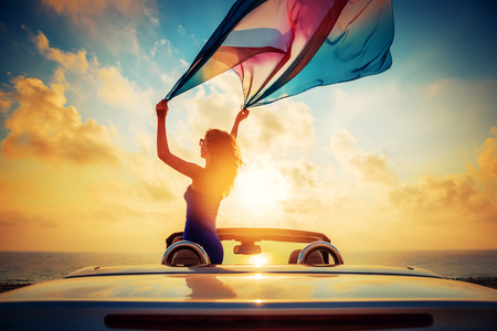 Silhouette of beautiful woman relaxing on the beach. Person having fun in cabriolet against blue sky background. Summer vacation and travel concept