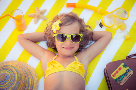 freedom concept: Happy child on the beach. Kid having fun outdoors. Summer vacation concept. Top view portrait