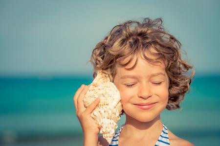 Dítě relaxaci na pláži proti moři a pozadí oblohy. Letní prázdniny a cestovní koncept