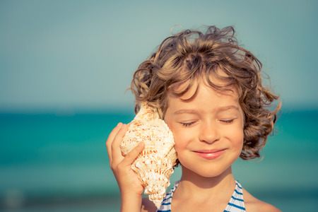 caracolas de mar: Niño que se relaja en la playa contra el mar y el cielo de fondo. vacaciones de verano y el concepto de viaje