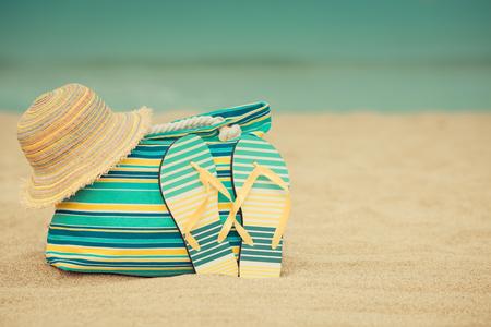 Flip-flop e borsa sulla spiaggia di sabbia contro il blu del mare e il cielo di sfondo. Concetto di vacanza estiva