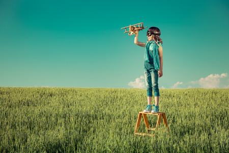 Happy kid playing with toy airplane outdoors in summer field. Travel and vacation concept. Imagination and freedom Stock fotó