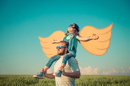 夏の畑で屋外の父で遊んで喜んでいる子供。旅行や休暇の概念。想像力と自由