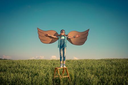 개념: 여름 필드에서 야외 행복한 아이. 여행 및 휴가 개념. 상상력과 자유