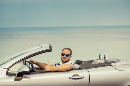 cabriolet: Happy man travel by car to the sea. Person having fun in cabriolet. Summer vacation concept