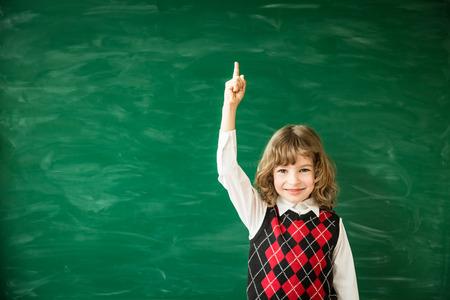 schoolchild: Back to school. Schoolchild in class. Happy kid against green blackboard. Idea and creativity concept Stock Photo