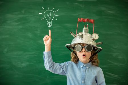 Terug naar school. Schoolkind met virtual reality headset in de klas. Grappig jong geitje tegen groene schoolbord. Innovatie en creativiteit concept Stockfoto