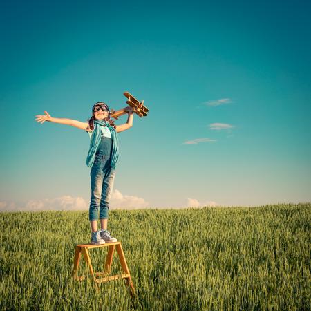 Bambino felice di giocare con aeroplano giocattolo all'aperto. Bambino nel campo estivo. Concetto di viaggio e di vacanza. L'immaginazione e la libertà
