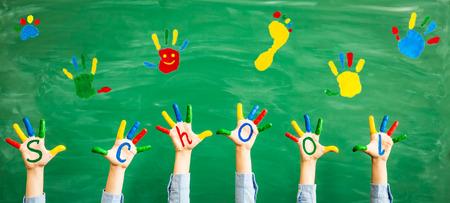 Terug naar school. Schoolkinderen in de klas. Handen tegen groene schoolbord. Onderwijs en creativiteit concept Stockfoto