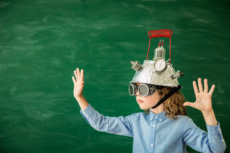 innovation concept: Back to school. Schoolchild with virtual reality headset in class. Funny kid against green blackboard. Innovation and creativity concept Stock Photo