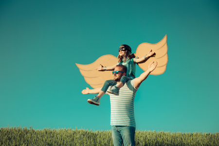 Happy child playing with father outdoors. Family having fun in summer field. Travel and vacation concept. Imagination and freedom