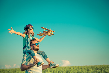 sports field: Happy child playing with father outdoors. Family having fun in summer field. Travel and vacation concept. Imagination and freedom