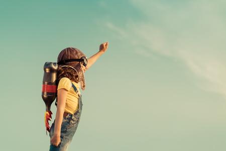 Kid met jet pack doen alsof superheld te zijn. Kinderen spelen in de zomer buiten. Succes, leider en winnaar begrip