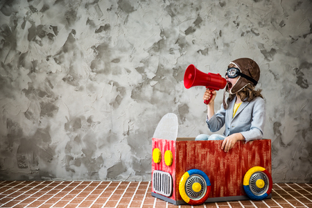 Child driving a car made of cardboard box. Kid having fun at home. Travel and vacation concept
