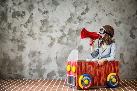 Niño que conduce un coche hecho de una caja de cartón. Cabrito que se divierten en el hogar. Concepto del recorrido y de las vacaciones