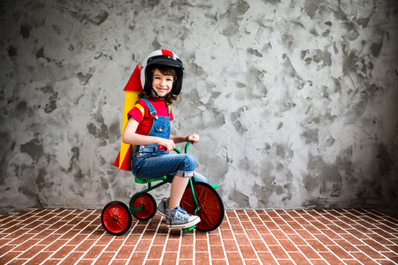 game drive: Child with cardboard rocket riding a retro bicycle. Kid having fun at home. Travel and vacation concept Stock Photo