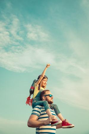 Kid con jet pack finta di essere supereroe. Bambino gioca con il padre in estate. Papà felice e figlio all'aperto. Successo, leader e vincitore concetto Archivio Fotografico - 61314047