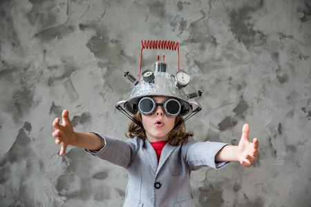 Retrato de niño pequeño pretende ser empresario. Niño con auriculares juguete de la realidad virtual en la oficina moderna desván. El éxito, el concepto creativo y la innovación tecnológica. Espacio en blanco para el texto