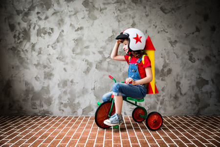Child with cardboard rocket riding a retro bicycle. Kid having fun at home. Travel and vacation concept Standard-Bild