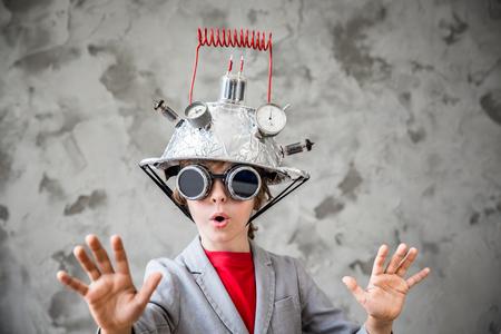 Portrait des jungen Kindes vorzutäuschen Geschäftsmann zu sein. Kind mit Spielzeug Virtual-Reality-Headset im modernen Loft-Büro. Erfolg, Kreativität und Innovation Technologie-Konzept. Kopieren Sie Platz für Ihren Text Standard-Bild