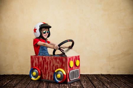 Kind het besturen van een auto gemaakt van kartonnen doos. Kid plezier thuis. Reizen en zomervakantie concept