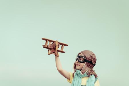 幸せな子供のおもちゃの飛行機で遊ぶ。夏空の背景に対して楽しんで子供。旅行と想像力の概念 写真素材