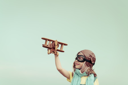Happy child playing with toy airplane. Kid having fun against summer sky background. Travel and imagination concept