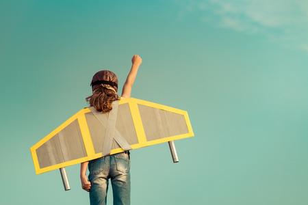 Kid con jet pack finta di essere supereroe. Bambino che gioca in estate all'aperto. Successo, leader e vincitore concetto Archivio Fotografico - 61237208