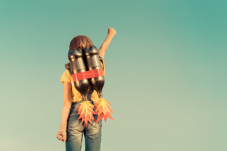 Kid with jet pack pretend to be superhero. Child playing in summer outdoors. Success, leader and winner concept Stockfoto