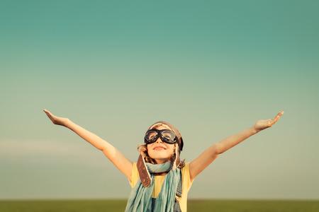 Glückliches Kind im Freien mit Spielzeug-Flugzeug zu spielen. Kid, die Spaß gegen Sommerhimmel Hintergrund. Reisen und Phantasie Konzept