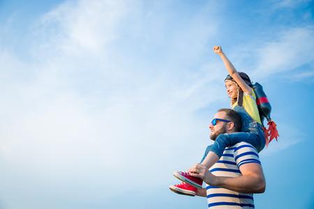ジェット パックを持つ子供は、スーパー ヒーローのふりをします。夏に父と遊ぶ子供。幸せなお父さんと息子の屋外。成功、リーダーおよび勝者の 写真素材
